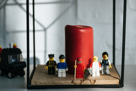KYIV, UKRAINE - MARCH 15, 2019: red figurine with can of gasoline and match standing with lego characters near candle