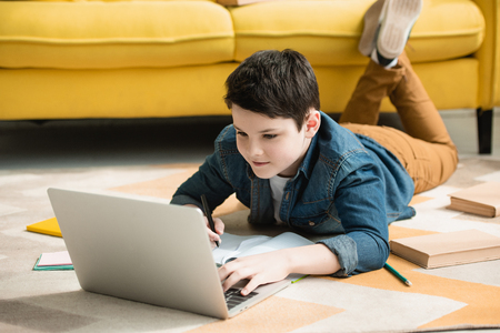 attentive boy lying on floor near books and using laptop while doing homework Stock fotó