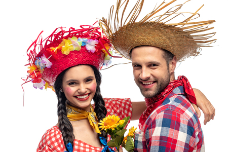 happy man and young woman in festive clothes with sunflowers looking at camera isolated on white