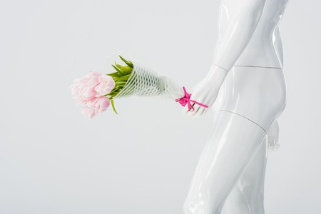 mannequin doll with bouquet of tulips isolated on grey