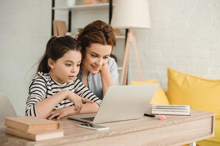 Madre e hija sorprendidas usando la computadora portátil mientras hacían los deberes juntos Foto de archivo