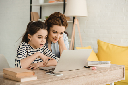 surprised mother and daughter using laptop while doing homework together Stock Photo
