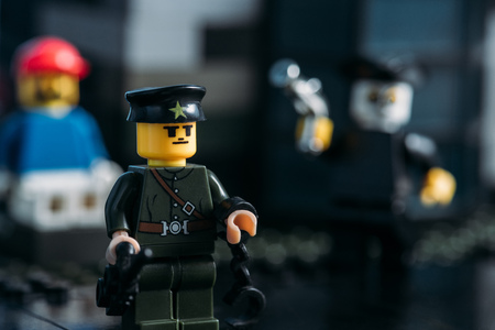 KYIV, UKRAINE - MARCH 15, 2019: selective focus of policeman lego figurine in hat and uniform