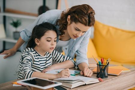 Madre atenta ayudando a la adorable hija haciendo los deberes escolares en casa