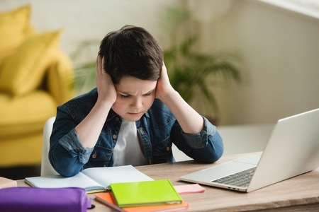 tired boy holding hands near head while sitting at table with notebooks and laptop