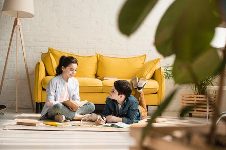 mise au point sélective d'un garçon mignon allongé sur le sol près d'une sœur assise tout en faisant des devoirs ensemble à la maison