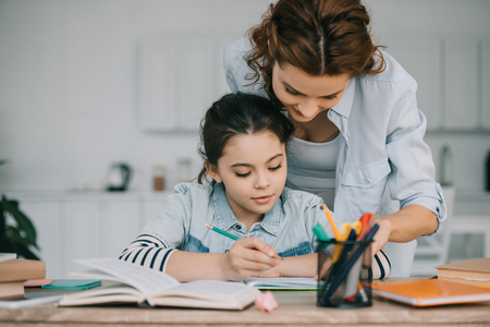 adorable child writing in copy book while doing schoolwork near mother