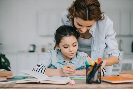 entzückendes Kind, das in Kopierbuch schreibt, während es Schularbeiten in der Nähe von Mutter macht