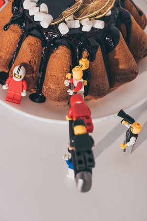 KYIV, UKRAINE - MARCH 15, 2019: plastic lego minifigures cutting cake with knife on white Redakční
