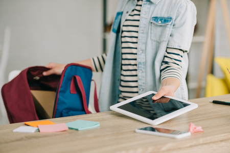 cropped view of schoolchild holding digital tablet with blank screen while packing back pack