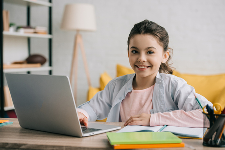happy child looking at camera while sitting at desk and using laptop at home Stock Photo