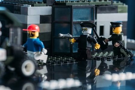 KYIV, UKRAINE - MARCH 15, 2019: pirate with gun and lego figurines during fight scene on lego blocks Editorial