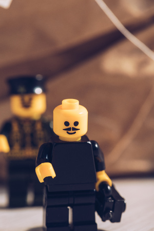 KYIV, UKRAINE - MARCH 15, 2019: selective focus of black lego figurine with moustache and smiley face