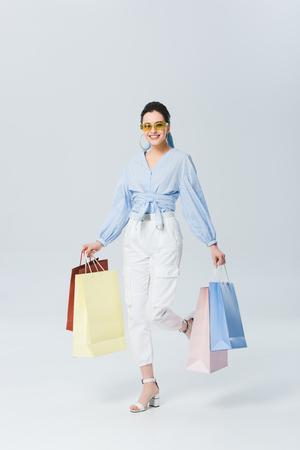 beautiful smiling girl with shopping bags walking on grey