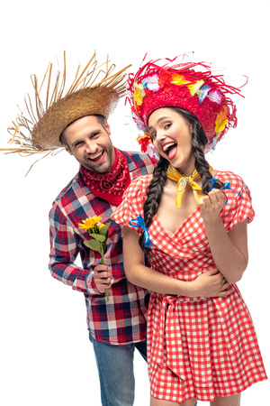 cheerful man and young woman in festive clothes with sunflower isolated on white