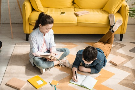 high angle view of adorable kids doing schoolwork on floor at home