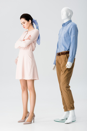 beautiful upset girl with crossed arms near mannequin on grey