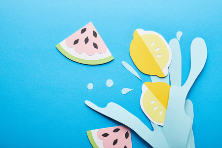 top view of paper cut water splash with lemons, leaves and watermelons on blue background Banco de Imagens