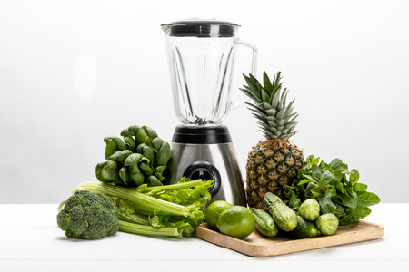green fresh spinach leaves near organic celery, cucumbers, broccoli fruits and blender on white