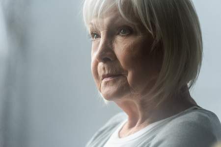 pensive senior woman with grey hair looking away