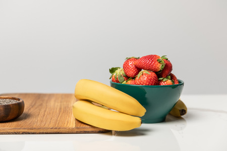 sweet and tasty strawberries in bowl near yellow bananas and cutting board on grey