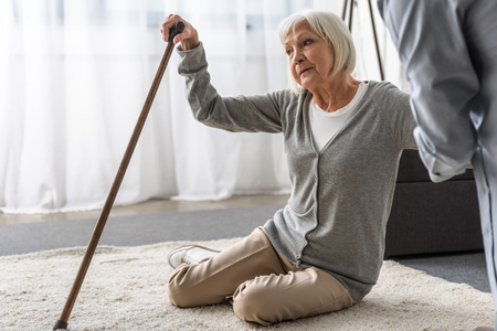 cropped view of man helping sick senior mother with cane fallen on floor Imagens