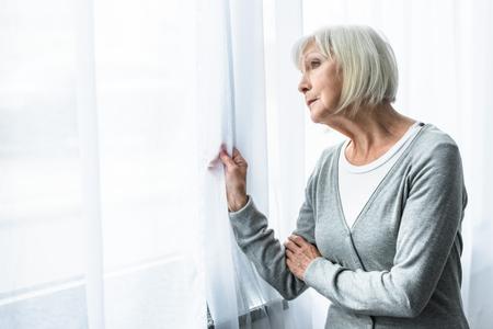 traurige ältere Frau mit grauen Haaren, die auf das Fenster schaut