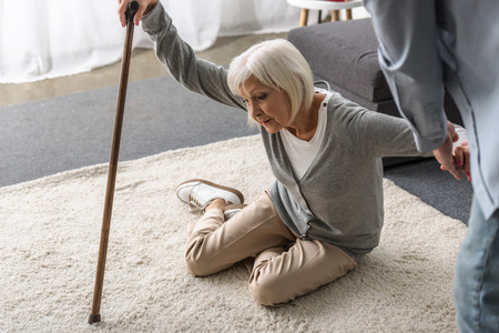cropped view of man helping sick senior mother with cane fallen on floor Stockfoto