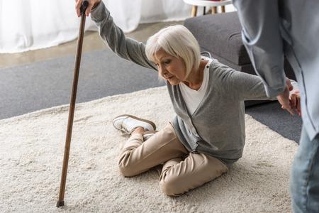 Vista recortada del hombre ayudando a la madre mayor enferma con bastón caído al suelo