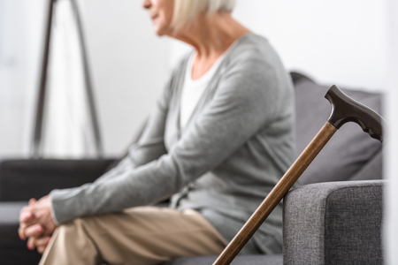 cropped view of senior woman with wooden cane on foreground 스톡 콘텐츠