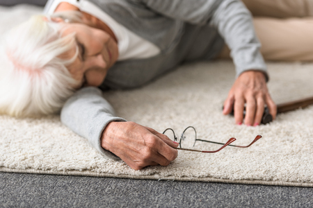 sick senior woman with glasses lying on carpet Imagens