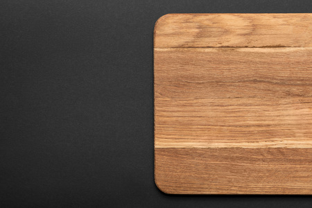 top view of empty wooden cutting board on black background