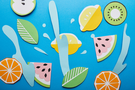 top view of paper cut water splashes with fruits on blue background Banco de Imagens