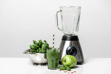 tasty green smoothie in glass with straw near fresh spinach leaves, apple and blender on white Stock Photo