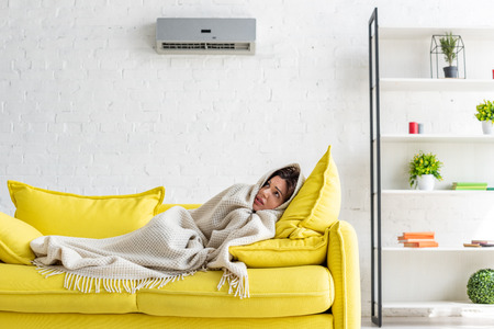 frozen woman warming with blanket while lying on yellow sofa under air conditioner at home Archivio Fotografico