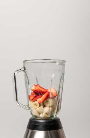 sweet strawberries and slices of ripe bananas in blender on grey