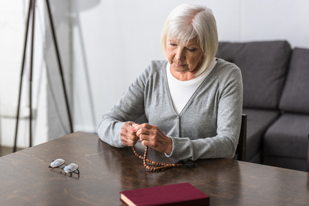 pensive senior woman sitting at table and holding rosary