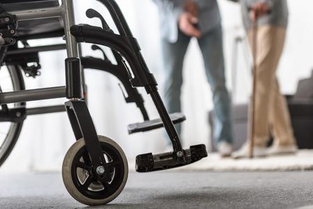 El enfoque selectivo del hijo adulto y la madre mayor con silla de ruedas en primer plano