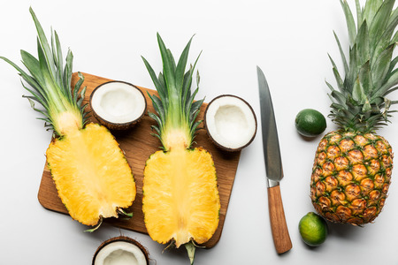 top view of cut ripe yellow pineapple on wooden chopping board near coconut halves, limes and knife on white background