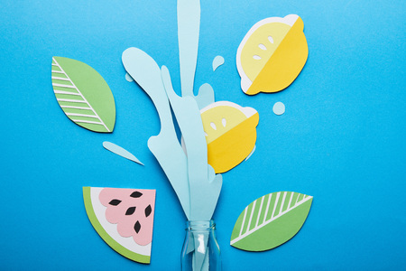 top view of bottle with paper cut water splash, lemons, leaves and watermelon on blue background Banco de Imagens