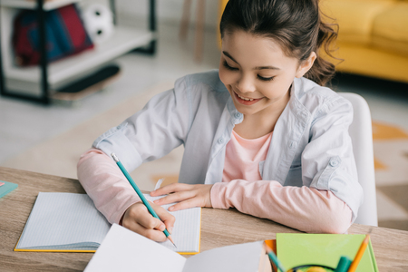 high angle view of adorable child doing homework and writing in notebook