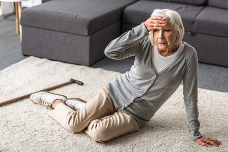 senior woman with migraine sitting on carpet and touching forehead with hand
