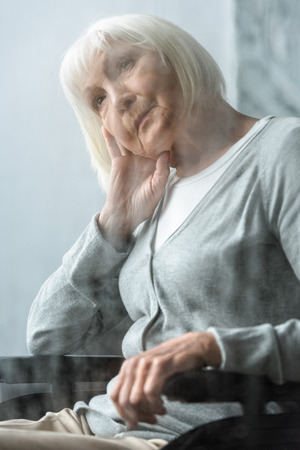 selective focus of pensive disabled senior woman with grey hair