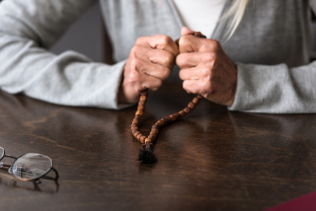 partial view of senior woman holding wooden rosary