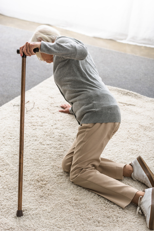 sick senior woman with wooden cane fallen on carpet