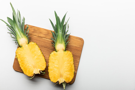 top view of cut ripe yellow pineapple on wooden chopping board on white background with copy space