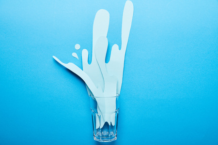 top view of glass with paper cut water splash on bright blue background with copy space
