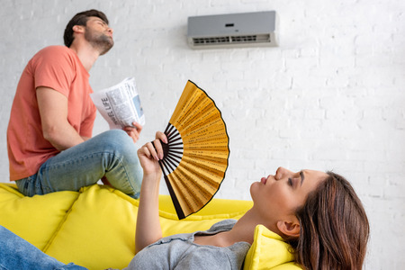 woman lying with hand fan and man with newspaper sitting on sofa under air conditioner at home Banque d'images