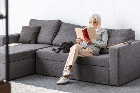 senior woman in glasses sitting on sofa and reading book in living room