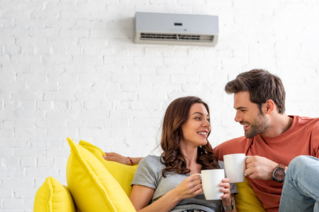 happy couple with cups sitting on sofa under air conditioner at home